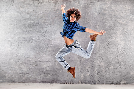 Young urban hip hop dancer jumping and dancing with grunge concrete wall background. Girl with afro hair.