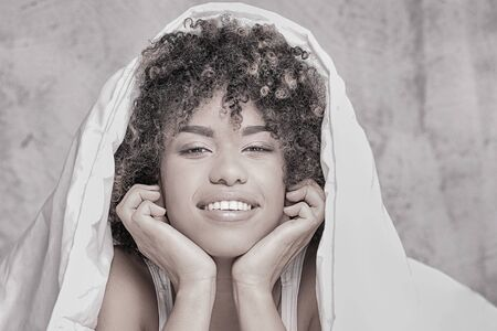 Young happy african american girl with afro lying in bed, relaxing, smiling to the camera. Stock Photo
