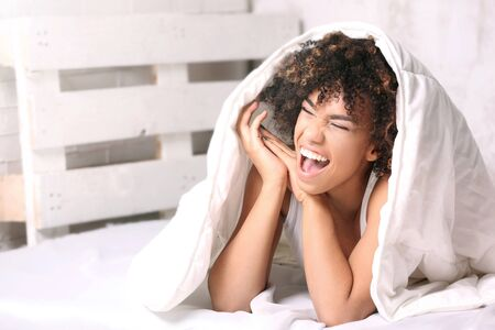Young happy african american girl with afro lying in bed, relaxing.