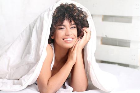 Junge glückliche African American Mädchen mit Afro im Bett liegend, entspannend, lächelnd in die Kamera. Standard-Bild - 69606798