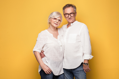 Beautiful happy senior couple posing together on yellow background.