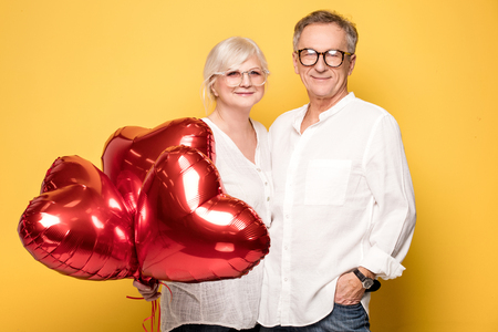 Beautiful happy senior couple posing together with red balloons, smiling.