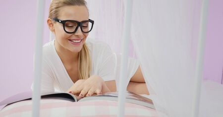 Beautiful young caucasian girl reading magazine in bed.
