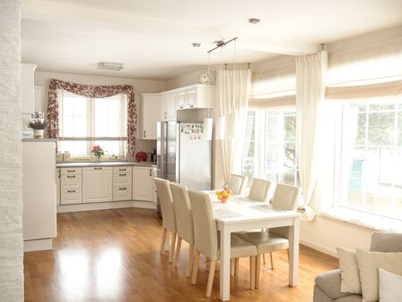 renovated: Beautiful bright kitchen interior with dining table and chairs. Stock Photo