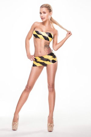 Attractive woman with sexy body in warning tape, studio shot.