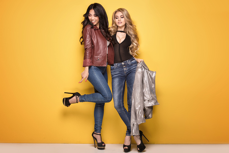 Two young beautiful girls posing together on yellow background. Fashionable asian woman with caucasian girlfriend.