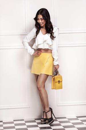 Fashionable attractive asian woman posing in studio, wearing yellow skirt.