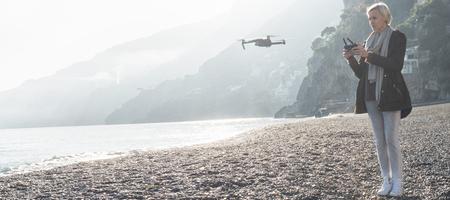 朝の太陽が降り注ぐビーチの上の飛行ドローン若い女性持株のコント ローラー。空中のビデオと写真のメーカーです。