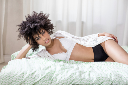 Sensual african american woman with afro hairstyle lying in bed, relaxing, looking at camera. Stock Photo