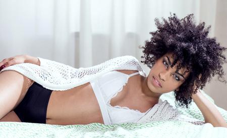 ベッドに横たわって、リラックス、カメラ目線のアフロの髪型と官能的なアフリカ系アメリカ人女性。 写真素材