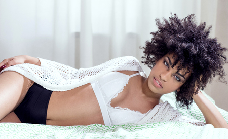 Sensuele afro-Amerikaanse vrouw met afro kapsel liggend in bed, ontspannen, camera kijken.