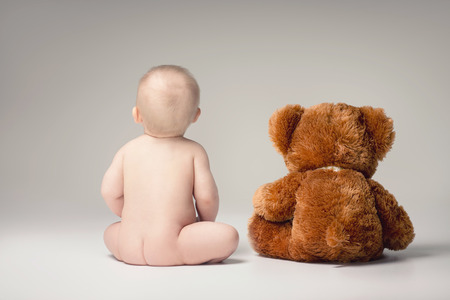 Little baby boy playing with his teddy bear in studio. Фото со стока