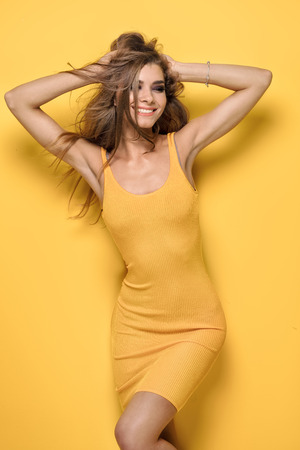 Attractive female model posing on yellow background, smiling.