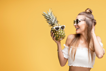 Young beautiful caucasian girl posing on yellow background, holding pineapples in hands.