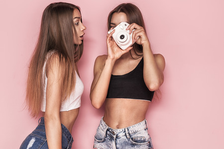 Young beautiful twins sisters taking photos, posing together on pink background.