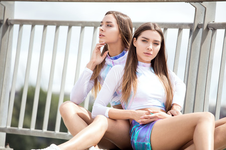 Twins sisters having fun together. Caucasian beautiful girls wearing fashionable clothes. Stock Photo