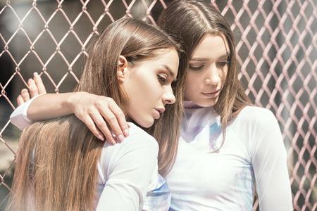 Due belle ragazze caucasiche alla moda dei gemelli che propongono all'aperto, giorno soleggiato di estate. Ritratto di bellezza del primo piano. Archivio Fotografico - 83446311