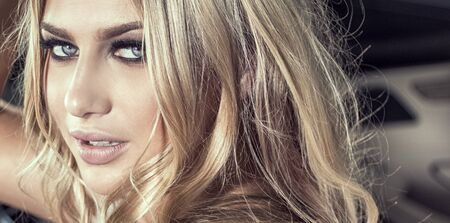 Beautiful sensual blonde caucasian woman in glamour makeup looking at camera. Banco de Imagens