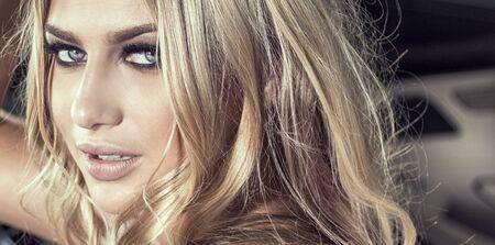 Hermosa mujer caucásica rubia sensual en maquillaje glamour mirando a cámara.