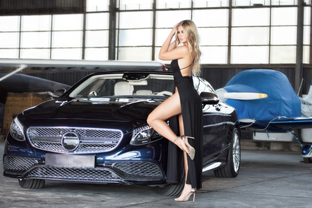 Elegant blonde beautiful woman standing by luxury car and small aeroplane. Girl wearing black dress. Reklamní fotografie