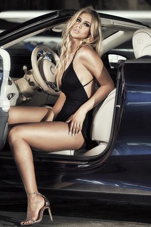 Elegant blonde beautiful woman sitting in luxury car. Girl wearing black dress.