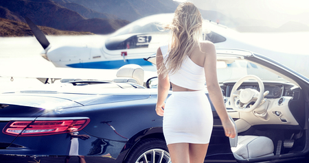 Sexy blonde woman at the airport near airplane and luxury car, sunny day.