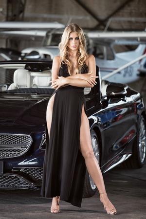 高級車や小型飛行機で立っているエレガントなブロンドの美しい女性。黒いドレスを着た少女。 写真素材