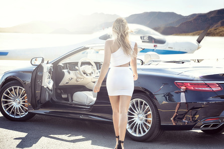 Sexy blonde woman at the airport near airplane and luxury car, sunny day. Reklamní fotografie - 85810469