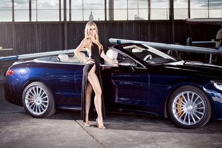 Elegant blonde beautiful woman standing by luxury car and small aeroplane. Girl wearing black dress. Stock Photo