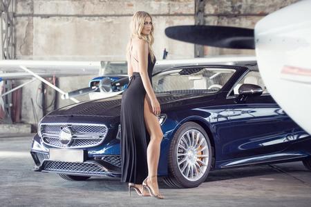 Elegante mulher loira bonita de pé por um carro de luxo e pequeno avião. Menina com vestido preto. Foto de archivo