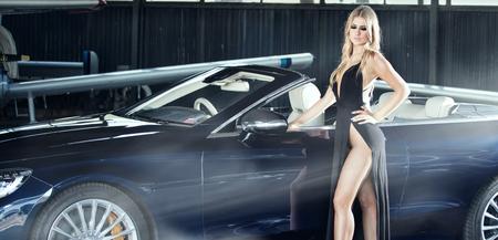 Elegant blonde beautiful womanposing with luxury car. Girl wearing black dress.