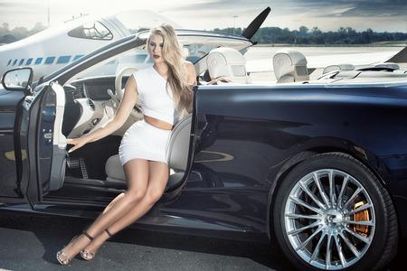 Sexy Blondine am Flughafen nahe Flugzeug und Luxusauto, sonniger Tag. Standard-Bild - 87225360
