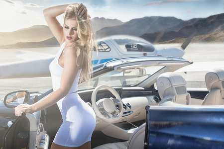 Sexy blonde woman at the airport near airplane and luxury car, sunny day. Reklamní fotografie - 87337771