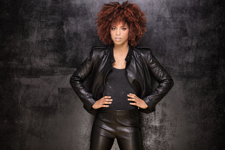 Fashionable young beautiful african american woman with afro hairstyle posing in black leather jacket.