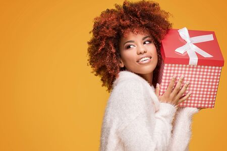 Beautiful african american girl with afro hairstyle holding gift box, smiling. Happy woman on yellow background. Stock Photo
