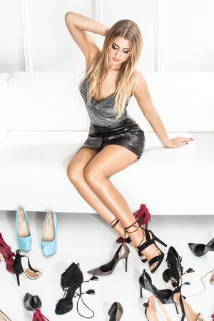 Beautiful sexy woman choosing shoes for a party.
