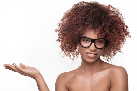Closeup portrait of Afro American woman with curly bushy hair, wearing eyeglasses , looking at camera with charming smile, holding hand on white empty background.