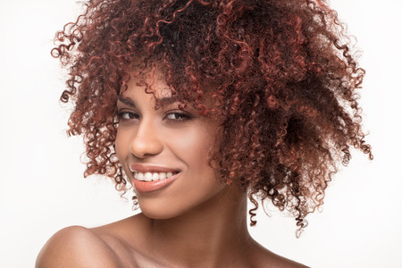 Beauty portrait of natural african american woman with afro hairstyle and toothy smile.