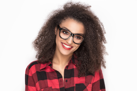 Happy beautiful african american girl posing in checkered shirt. White background.