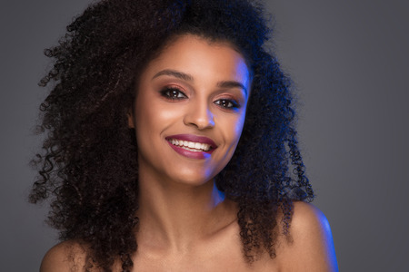 Beauty portrait of smiling dark skin young woman with curly afro hair and glamour makeup. Studio  shot on gray background, copy space.
