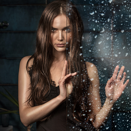 Brunette young beautiful woman with long hair posing over water drops, looking at camera.