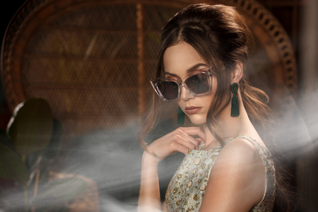 Fashion style photo of elegant attractive woman. Brunette retro look lady wearing earrings and fashionable sunglasses.