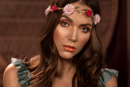 Fashion style photo of beautiful young woman in boho style clothes. Girl wearing flower hairband. Trendy curly hairstyle and glamour natural makeup. Reklamní fotografie