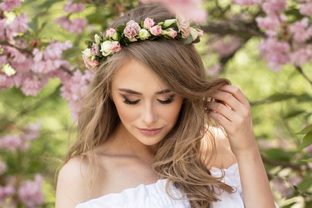 Attractive beautiful caucasian blonde woman posing in spring blossom flowers in blooming garden. Sunny day. Girl with roses on head. Beauty portrait. 写真素材