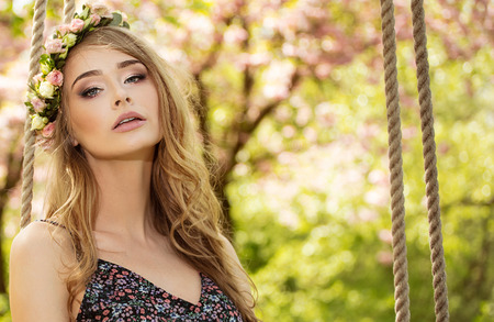 Attractive beautiful caucasian blonde woman posing in spring blooming garden. Sunny day. Girl with flowers on head swinging, wearing maxi dress. Standard-Bild