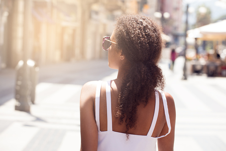 Back view on beautiful african american girl with long curly hair walking on the italian street at sunny summer day. Leisure holiday time.
