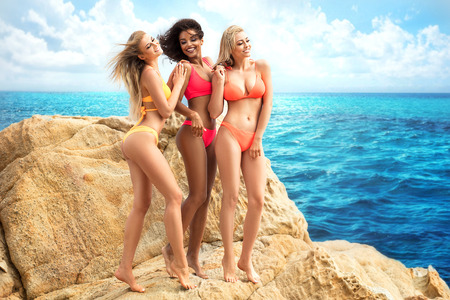 Group of multi ethnic beautiful girls posing on the rocky beach at sunny summer day.