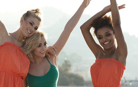 Group of happy friends having fun on the beach on sunset. Joyful girls on summer vacation.