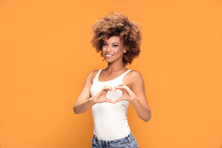 Beautiful young african american woman gesturing heart shape with hands on yellow background. Stockfoto