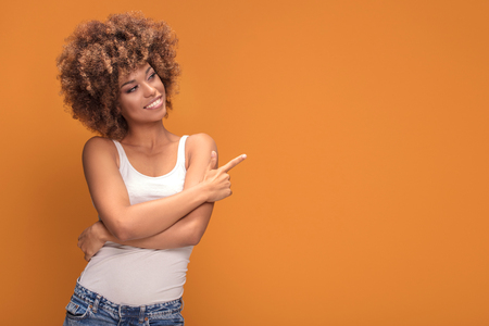 Colorful photo of smiling beautiful african american woman points her finger at the yellow background.